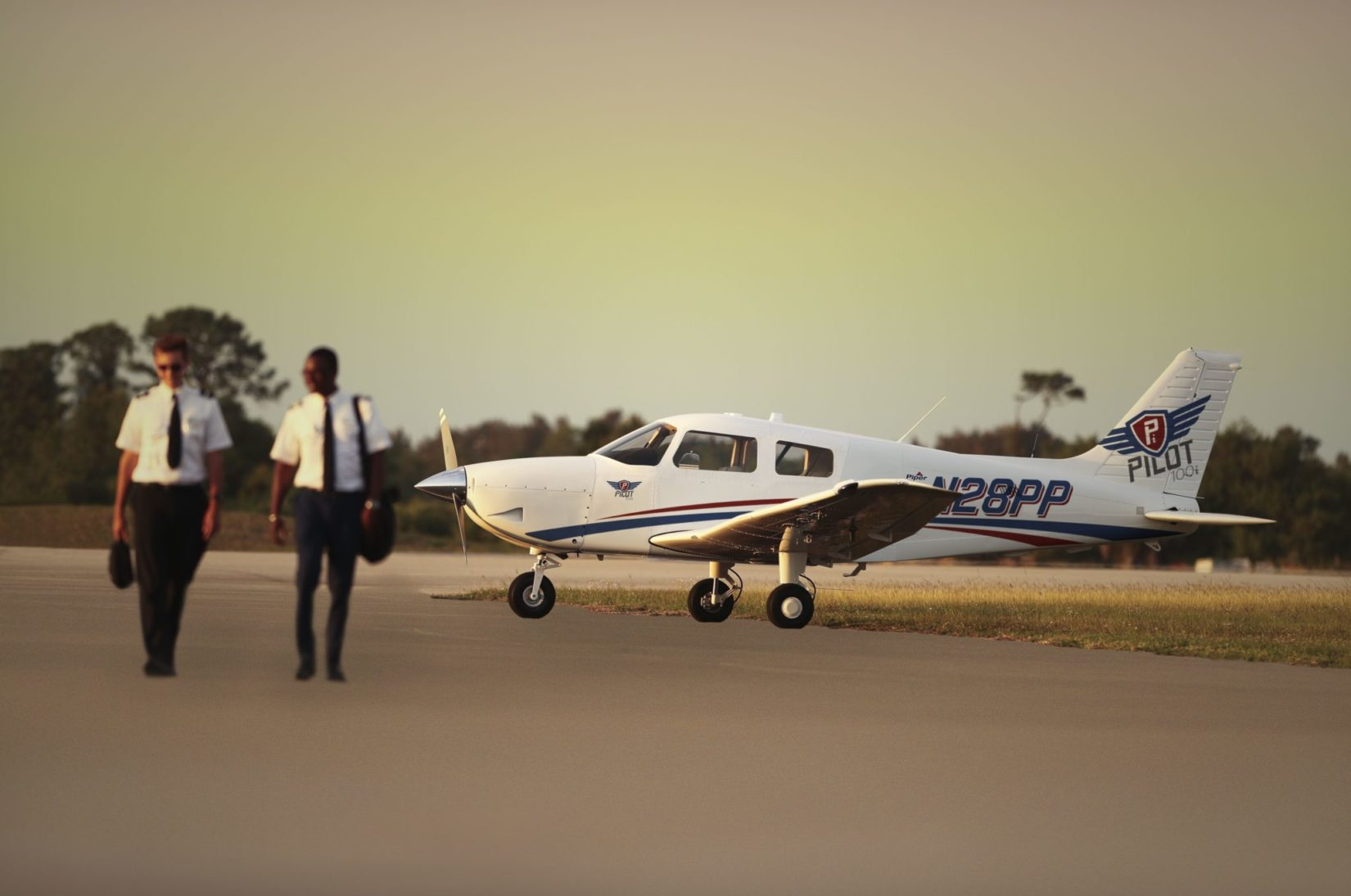 Two pilots walking on the runway next to the Piper Pilot 100i aircraft