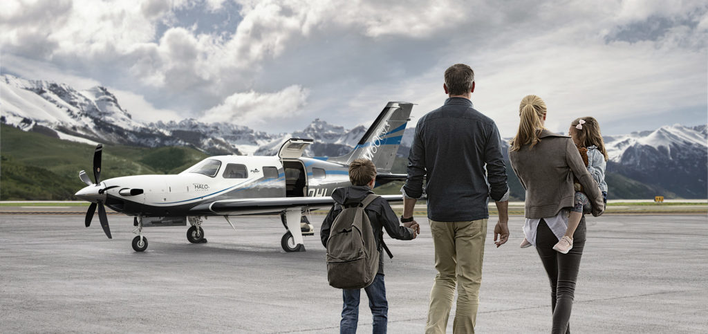 Family holding hands and walking toward a Piper aircraft