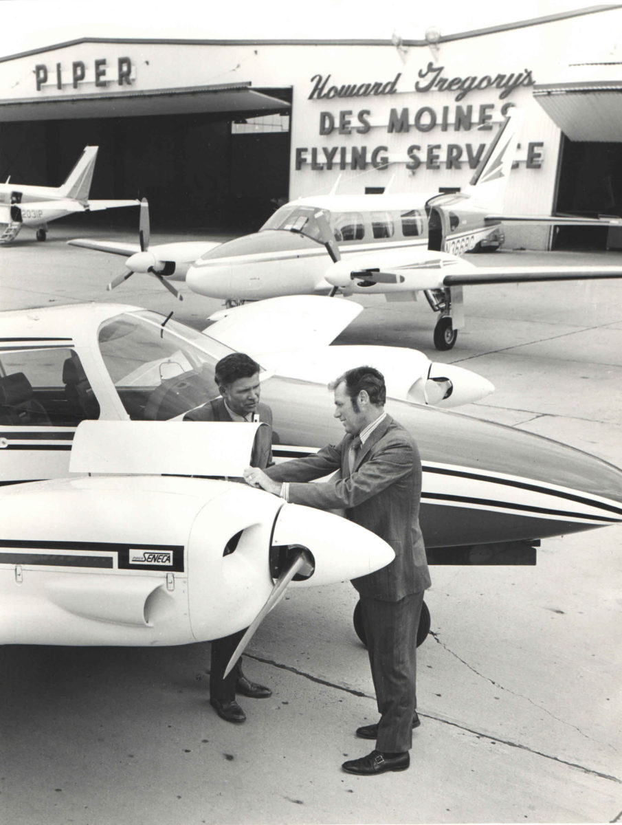 Sales representatives beside a Seneca in front of the Des Moines Flying Services hangar
