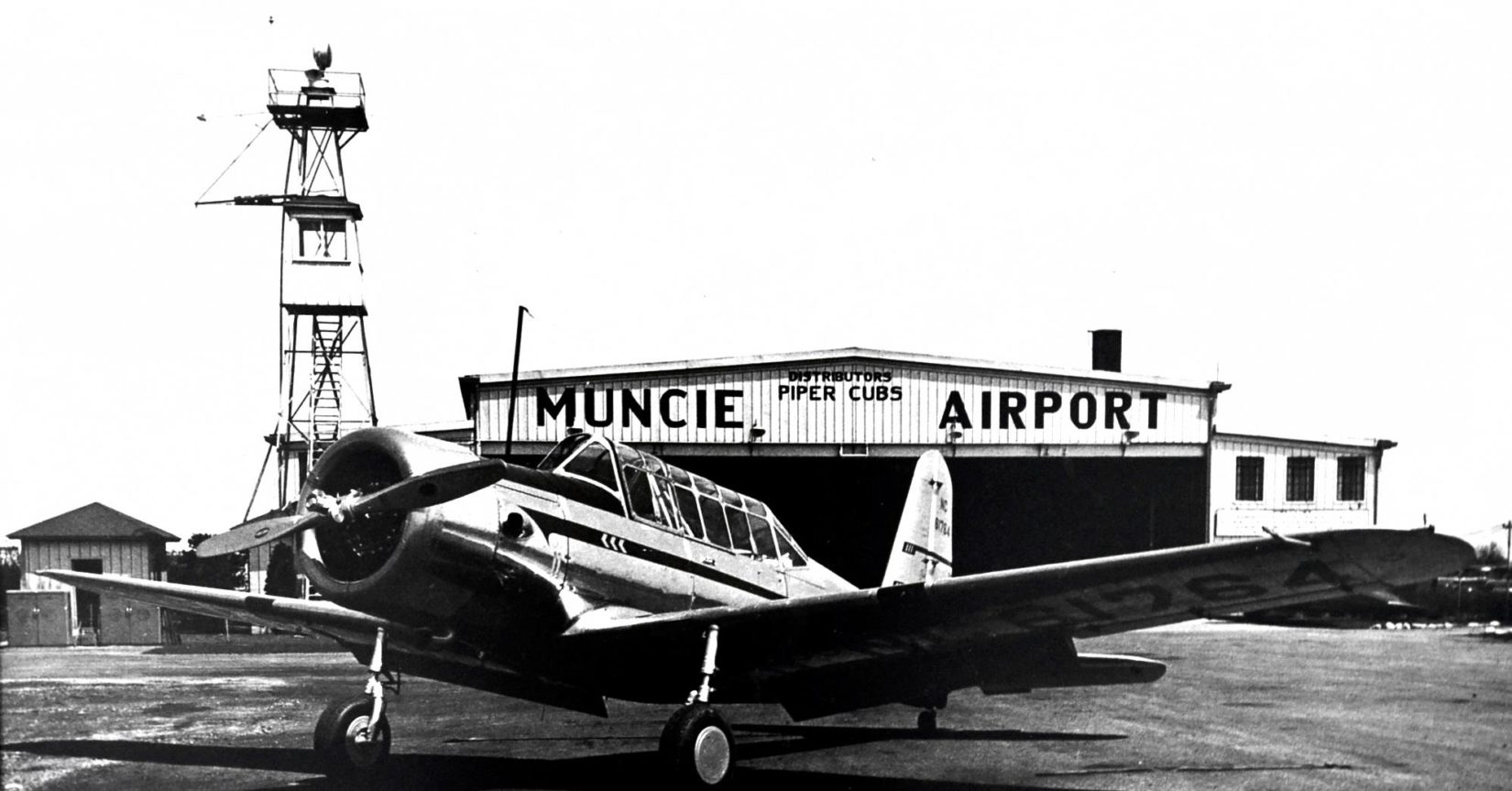 Historical photo of an aircraft in front of a Muncie hangar