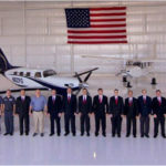 Piper Aircraft team in the hangar with an American flag in the background