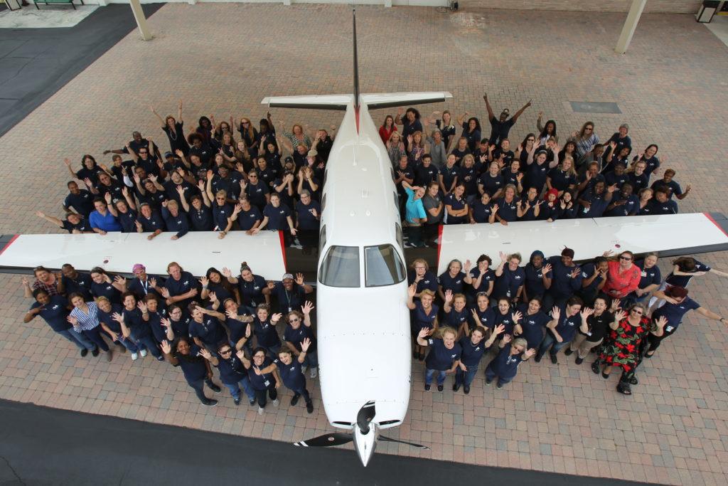 Piper Aircraft employees standing next to an aircraft