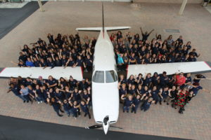 Piper Aircraft employees standing next to an aircraft