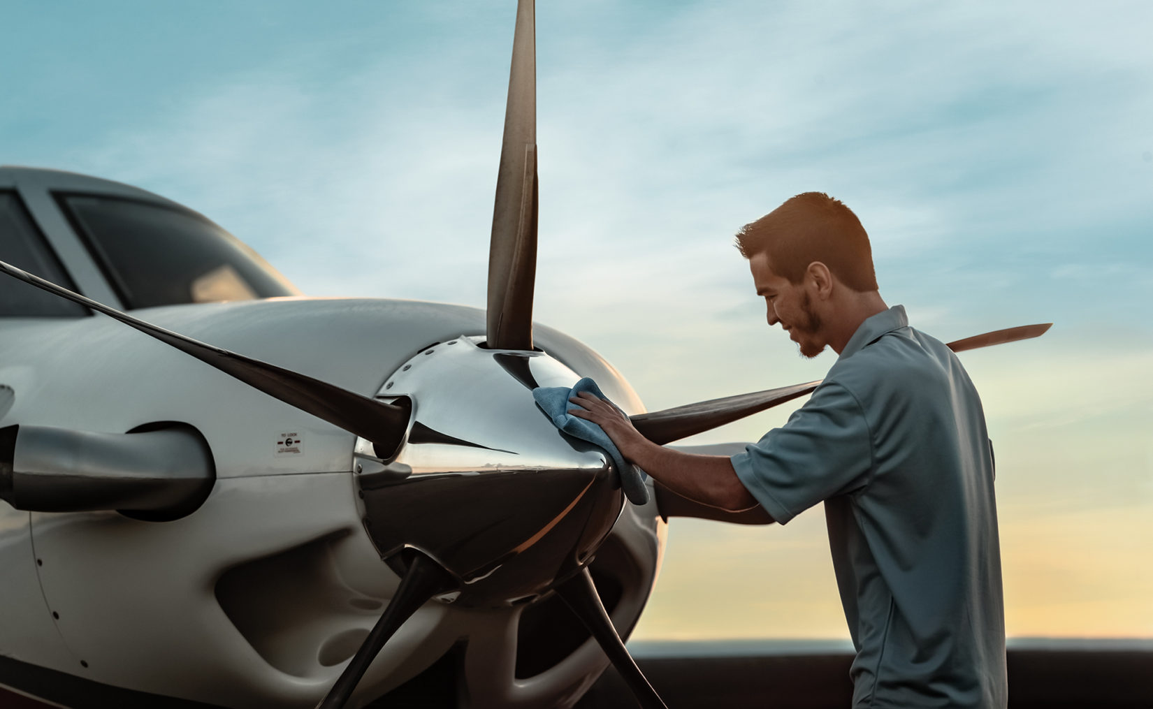 Man wiping the nose of a Piper Aircraft