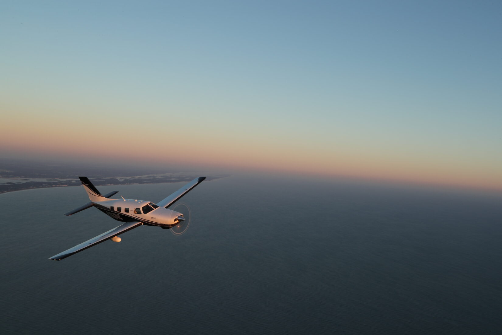 Piper M350 flying over coastline at sunset