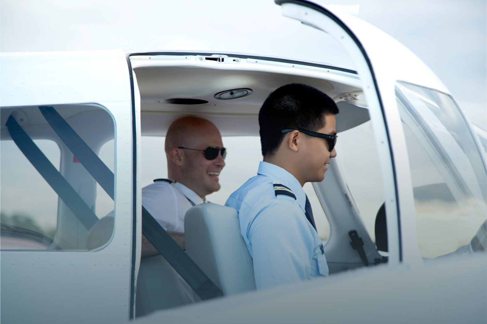 Pilot sitting in cockpit with student pilot